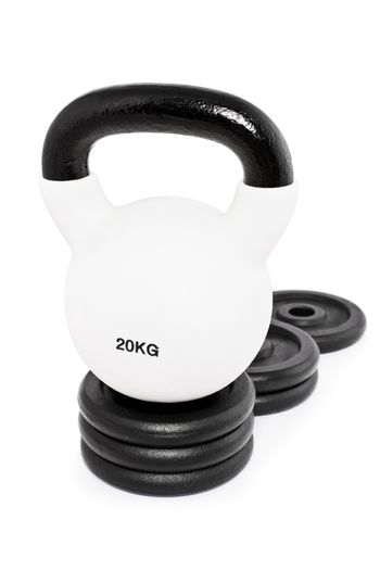 White heavy kettlebell on a pedestal of weight plates, isolated on a white background. Heavy win.