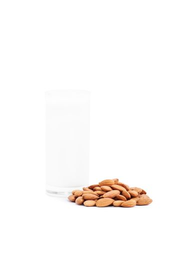 Close up shot of a glass of almond milk with a heap of almonds, isolated on white background.
