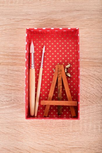 Small easel and paint brushes in a box on wooden background.