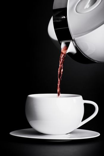 Pouring tea on black background. Low key photograph of a tea pouring in a cup from a tea pot.