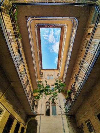 Bottom up view of the sky from an inner courtyard square of a building in Budapest. Geometric view of an inner square of a residential building.
