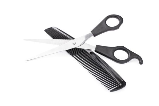 Crossed scissors and comb, isolated on white background.