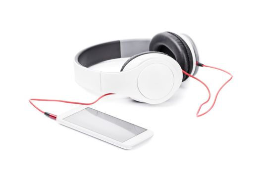 Close up of smartphone and headphones, isolated on white background.