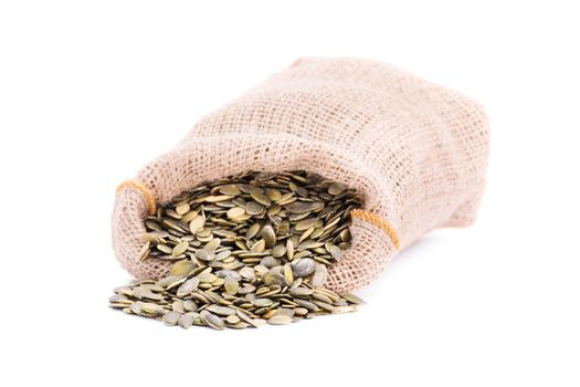 Close up shot of spilled burlap sack of pumpkin seeds, isolated on white background.