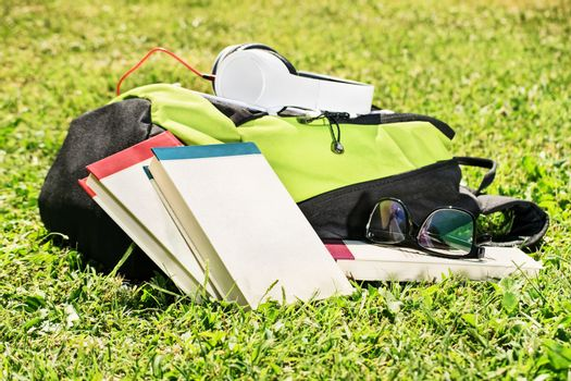 Taking a break after studies. Student backpack with books scattered around, glasses and headphones on a green grass.