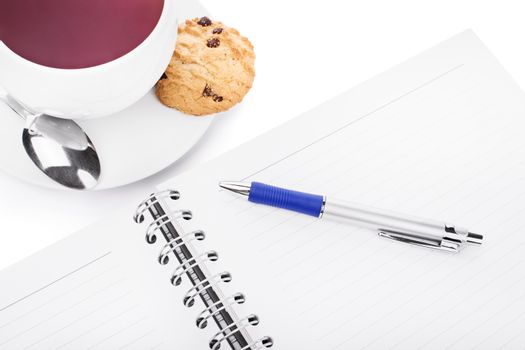 Pen and notebook with a cup of tea, chocolate chip cookie and a small spoon, isolated on white background.