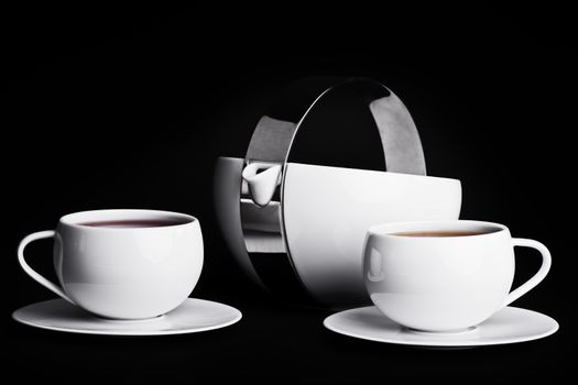 Tea pot with two cups of tea on black background. Low key tea set.