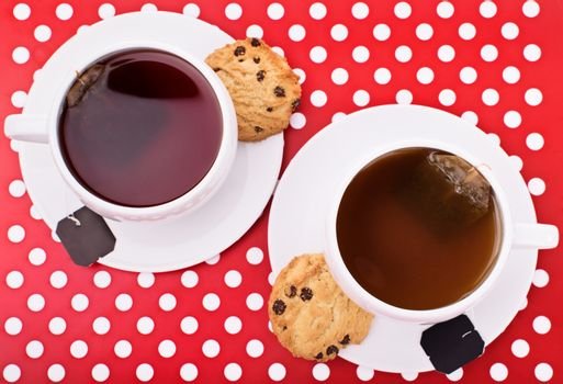 Close-up top view shot of two cups of tea with chocolate chip cookies on a platter.