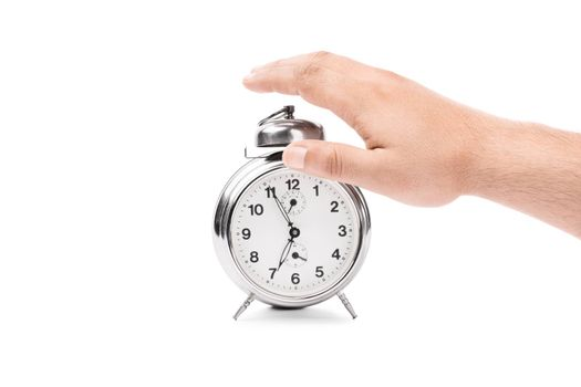 Hand reaching out to turn off the alarm from the alarm clock, isolated on white background.