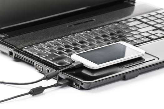 Data transfer between devices. Close up shot of mobile phone connected to a laptop with a usb cable, isolated on white background.