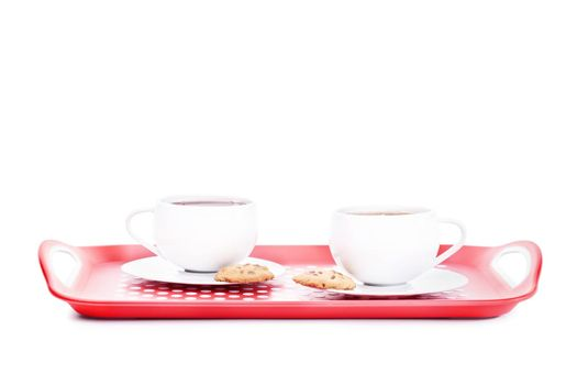 Two cups of tea with cookies on a platter, isolated on white background.
