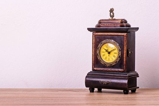 Antique Victorian clock on a wooden table.
