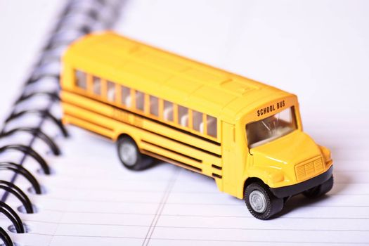 Close up shot of a toy school bus on top of an open spiral notebook.