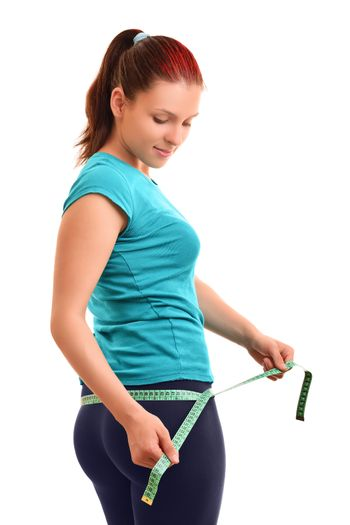 Beautiful fit young woman in sports outfit measuring her hips with a measuring tape, isolated on white background.