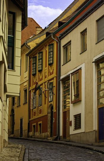 Narrow cobblestone street with colorful old town houses in Budapest.