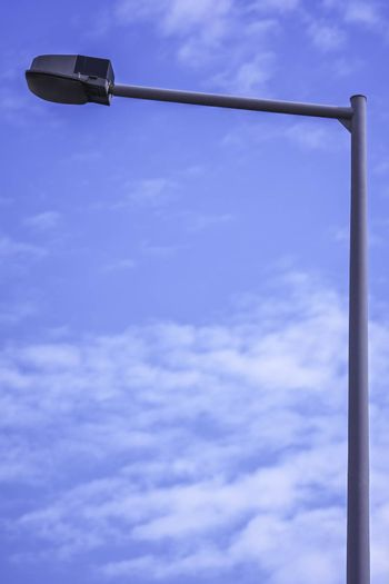 Close up shot of a single street light with a clear blue sky in the background.