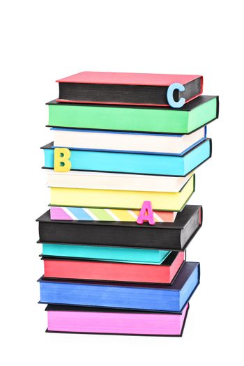 Stack of colorful books witch different sprayed edges and scattered letters spelling ABC, isolated on white background.