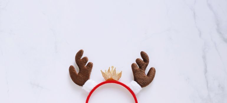 Fancy headband with reindeer antler decorative shape for christmas party and celebration on white marble background, banner style for text