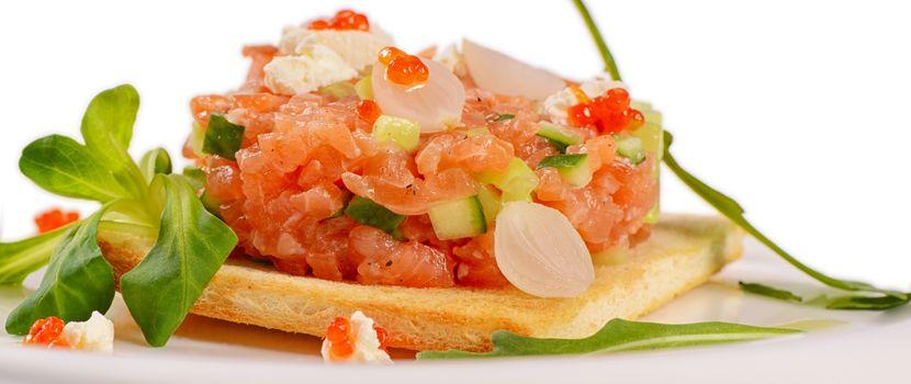 The tartare of salmon on a bun close up