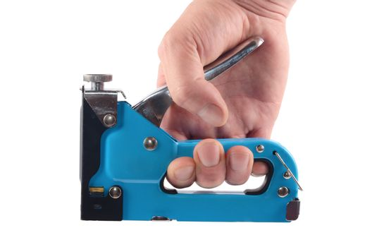 The furniture stapler in a man's hand isolated