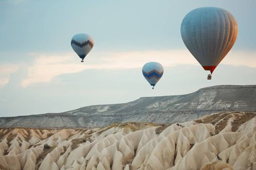 Three hot air balloons flying over the rocks of Cappadocia, Turkey