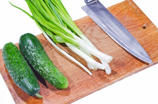 fresh cucumbers and green onions on a cutting board