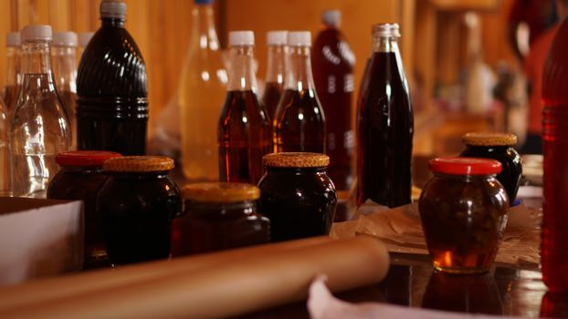 Homemade mead bottles on the shelf of an outdoor market. honey wine