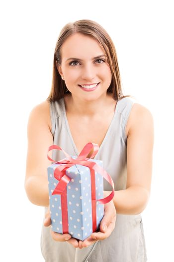 Beautiful young woman holding a wrapped gift, making an impression she's giving it to you, isolated on white background.
