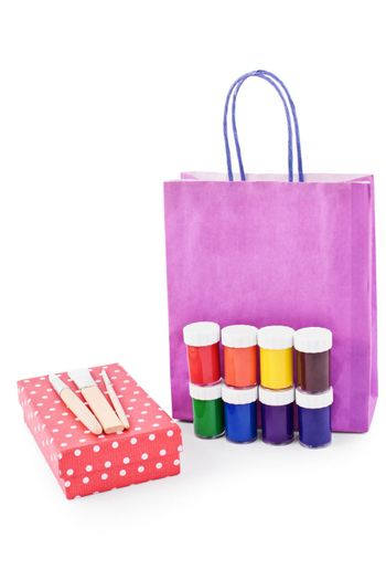 Paint brushes, paint vials, gift box and a gift bag isolated on white background.