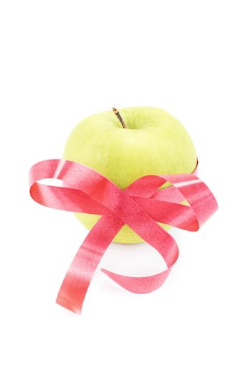 Green apple wrapped with red ribbon isolated on white background