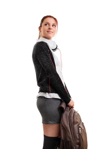 A portrait of a smiling female student in uniform with headphones, holding a backpack, isolated on white background. I can't wait to go back to school.
