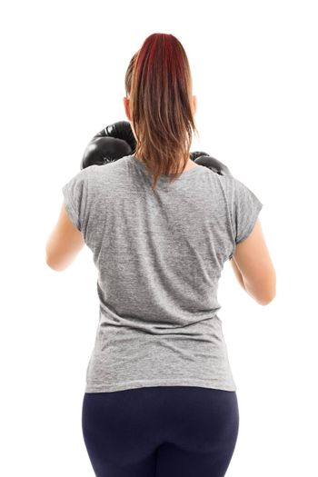 Muscular female boxer with her guard up, photographed from behind, isolated on a white background.