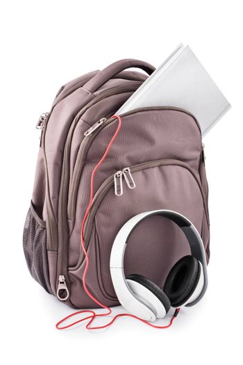 Backpack with headphones and notebook, isolated on white background.