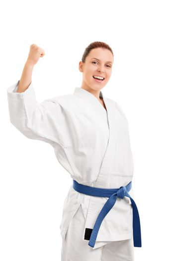A portrait of a beautiful young girl in a kimono with blue belt cheering after her victory, isolated on white background.