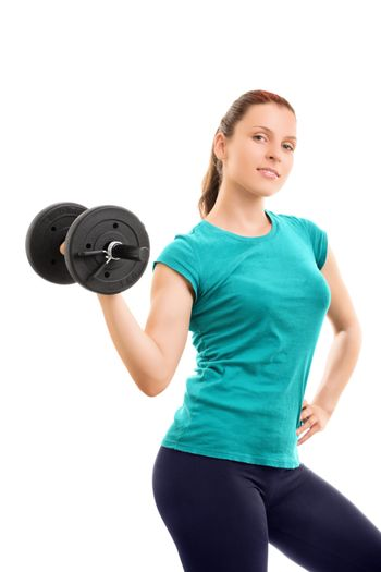 A portrait of a beautiful fit girl smiling and lifting a dumbbell, isolated on white background. Beautiful fit young girl holding a dumbbell, isolated on white background.