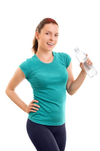 A portrait of a beautiful smiling young girl in fitness clothes holding a water bottle, isolated on white background.