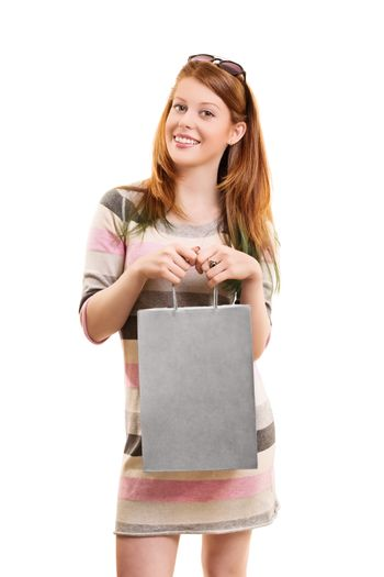 A portrait of a beautiful young girl holding a shopping bag in front of her, isolated on white background.