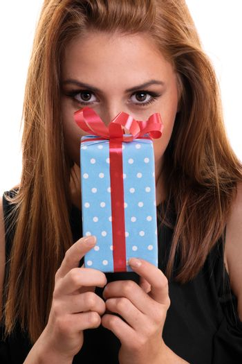 A portrait of a beautiful young girl holding a gift, isolated on white background.
