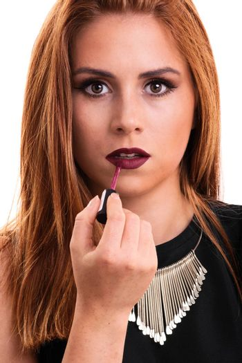 A portrait of a beautiful young girl putting lipstick, isolated on white background.