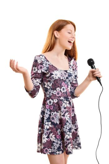 A portrait of a beautiful young girl holding a microphone singing, isolated on white background.