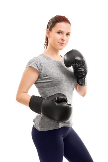 A portrait of a beautiful young girl with boxing gloves in a stance, isolated on white background.