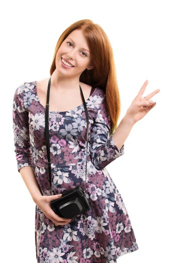 A portrait of a beautiful young girl holding a vintage camera and gesturing with her hand, isolated on white background.