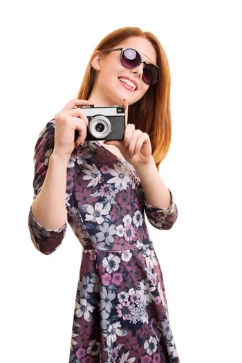 A portrait of a beautiful young girl taking a photo with a vintage camera, isolated on white background.