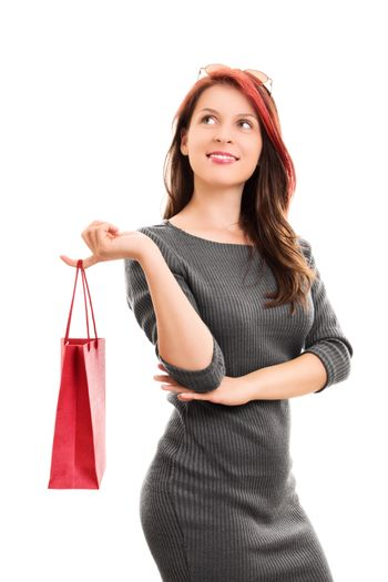 A portrait shot of a beautiful young girl in a dress, holding a shopping bag, isolated on white background.