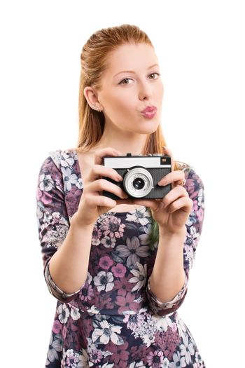 A portrait of a beautiful young girl taking a picture with a vintage camera, isolated on white background.