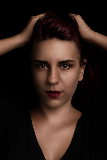 Low key sensual beauty portrait of a red haired young woman holding her hair on black background.