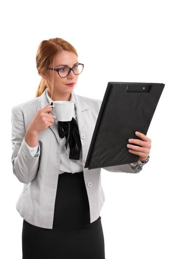 Morning meeting preparation. A portrait of a businesswoman, holding a cup of coffee and a clipboard, isolated on white background.