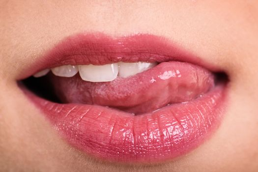 Close up shot of beautiful woman mouth with tongue out.