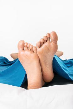 Close-up shot of female feet under the blanket, isolated on white background.