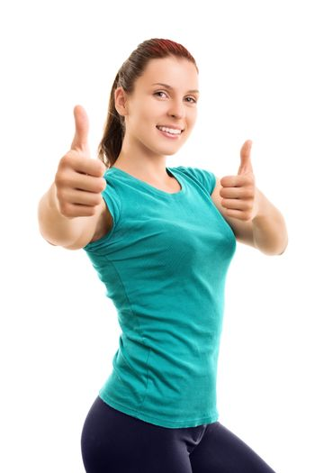Slim and fit. You should try it. Beautiful smiling young girl in fitness clothes giving thumbs up, isolated on white background.